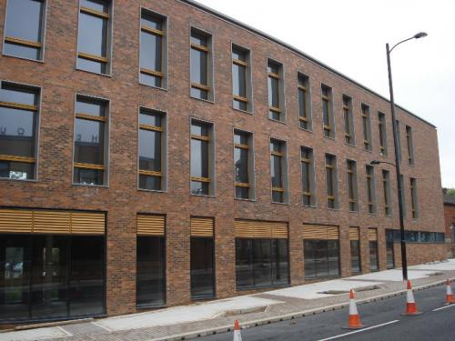 large brick building with wooden cladding surrounding windows