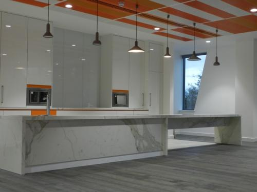 orange ceiling cladding above white marble kitchen with orange accents