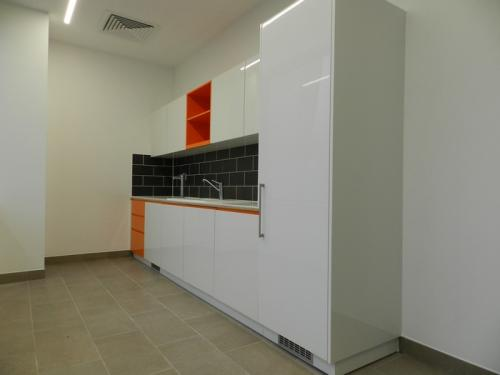 white kitchen area with orange accents