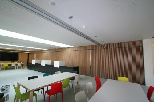 wooden cladding on wall and tables with coloured chairs