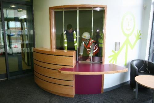 curved wood and pink reception desk
